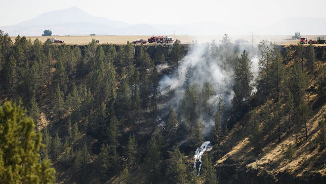 Smoke billows as emergency services work to extinguish a plane crash in Willow Creek Canyon, one mile south of the Madras Municipal Airport, on Saturday, Aug. 19, 2017.