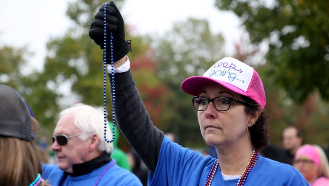 Kim Kinney, of Salem, holds up beads to support suicide awareness during the Out of the Darkness walk for suicide prevention and awareness at Riverfront Park in Salem on Saturday, Oct. 14, 2017. Kinney walked in memory of her partner who died by suicide in 2015.
