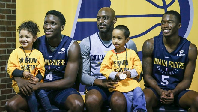 From left, Aryelle Shumpert, 5, Indiana Pacers guard Victor Oladipo (4), Indiana Pacers guard Damien Wilkins (12), Cayden Shumpert, 4, and Indiana Pacers guard Edmond Sumner (5) pose for a picture during the Indiana Pacers FanJam at Banker's Life Fieldhouse, Indianapolis, Sunday, Oct. 15, 2017.