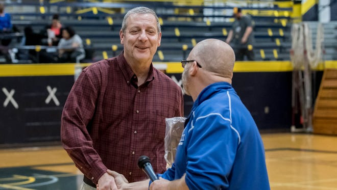 Russ Bortell, left, longtime coach and admissions recruiter at Kellogg Community College was given an on-court presentation in recognition of his 30 years at the college. Althletic Director Tom Shaw at right.