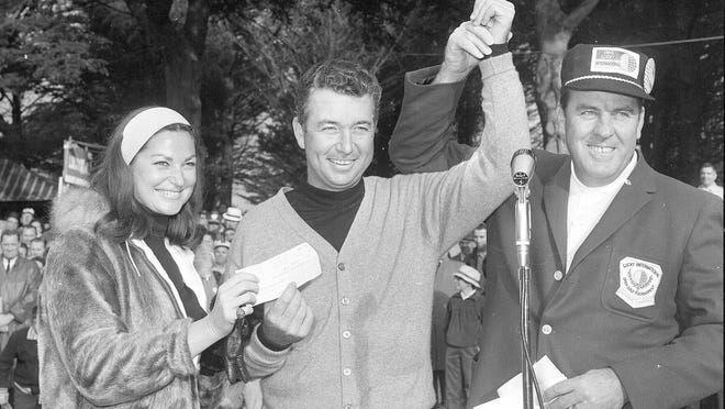 John Keane, right, general chairman of the Lucky International Golf Tournament, raises the hand of Ken Venturi after presenting him with the winners check of $8,500 at Harding Park, January 31, 1966 in San Francisco, Calif. Helping Ken hold the check is his wife, Connie. Venturi carded a 66 for the final round for a total of 273.