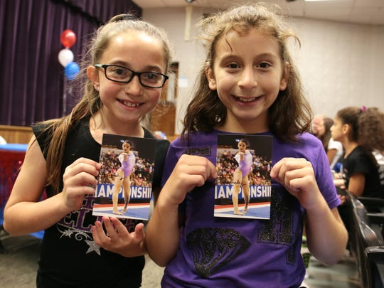 Jordan Bechert, 10, left, and Hailey Cosentino, 10, both of Old Bridge, pose with autographed photos of Laurie Hernandez at a township-wide sendoff at Old Bridge High School on July 14, 2016 for Hernandez, 16, who will be competing in Rio as part of the U.S. Women's Gymnastics Team.