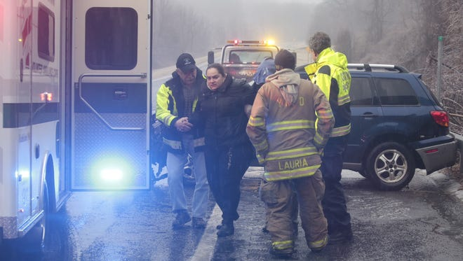 A woman being helped from her car after she crashed due to icy road conditions on the Taconic  car accident Parkway in Yorktown Sunday.