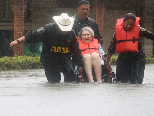 Precinct 6 Deputy Constables Sgt. Paul Fernandez, left, Sgt. Michael Tran and Sgt. Radha Patel help an elderly woman amid rising water on North MacGregor Way, near Brays Bayou, after heavy rains from the remnants of Hurricane Harvey Sunday in Houston.