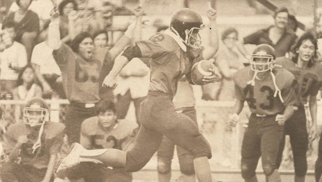 Voc. Tech QB Paul Paulino (12) runs for glory in a game between the Voc Tech Friars and the John F. Kennedy Green Machine (coached by Mike Hopkins) in an Oct. 13, 1979 game. Voc Tech wore black pants and red jerseys with black helmets, and was a combination of Vocational Technical school and Father Duenas High. The team was coached by Mike Grandinetti, who once was the  offensive oordinator under Jerry Fornelia. Thanks to coach Loring Cruz for his insight.