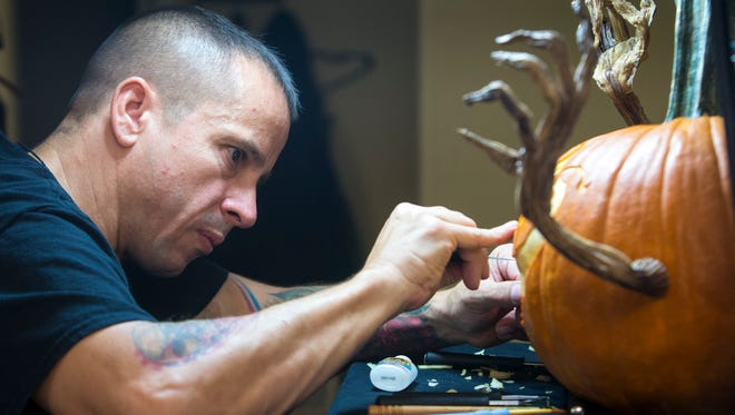 Wicked-looking appendages reach out from a pumpkin as Ray Villafane adds finishing details. The renowned carver's pieces are in demand nationally and internationally this time of year. By December, he will have transformed more than 100 pumpkins into monsters, ghoulish visages and even fun, realistic faces.