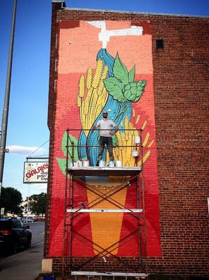 Artist Nick Goettling poses with the mural he is creating in downtown Stevens Point at the Comics Games & More building at 925 Clark St. A public dedication for the mural will be held July 26, 2017.