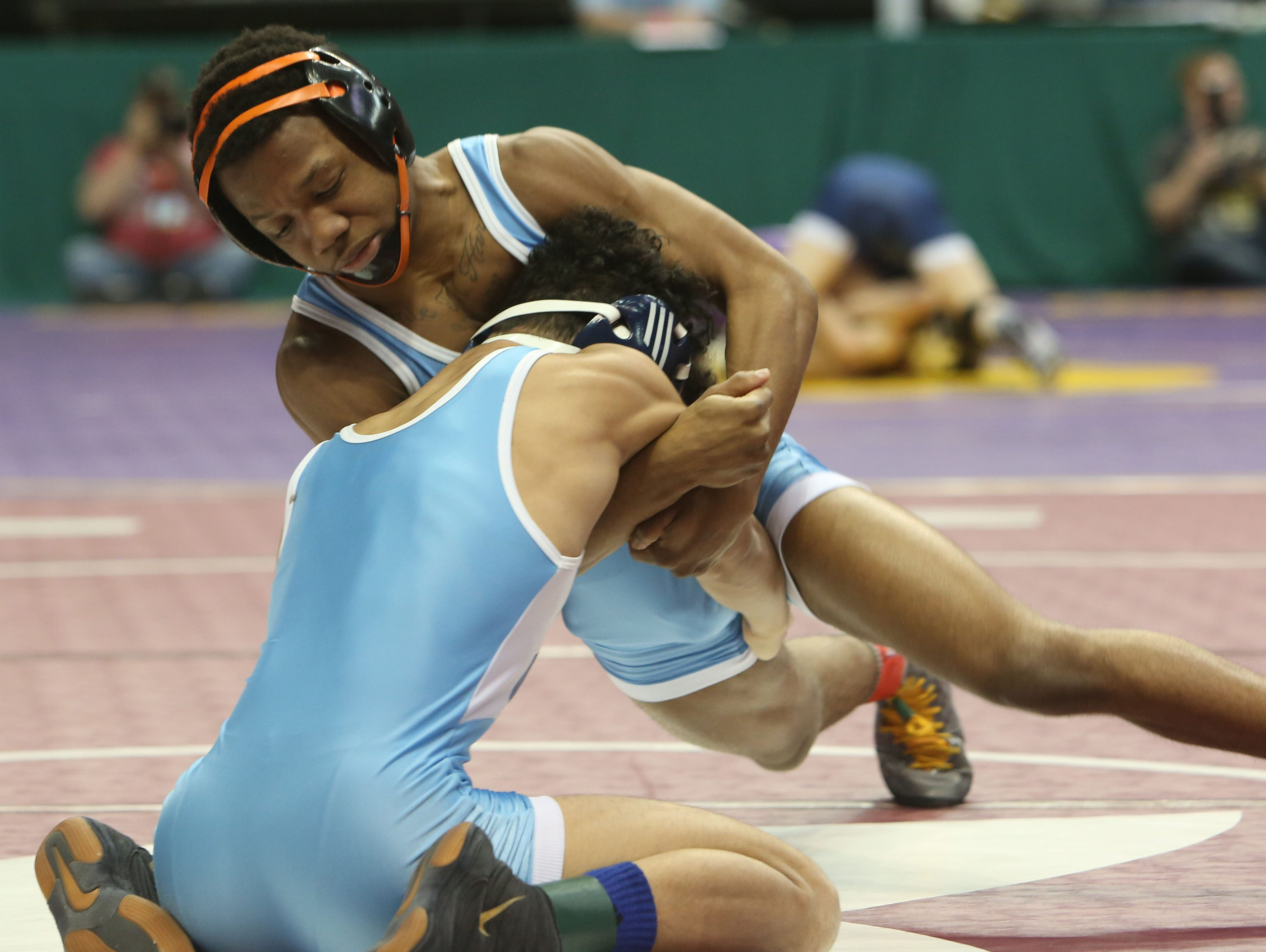 From left, East Ramapo's Trey Wardlaw on his way to defeating Yonkers' Justin Lopez in the 106-pound weight class during the quarterfinals of the New York State wrestling championships at the Times Union Center in Albany Feb. 26, 2016.