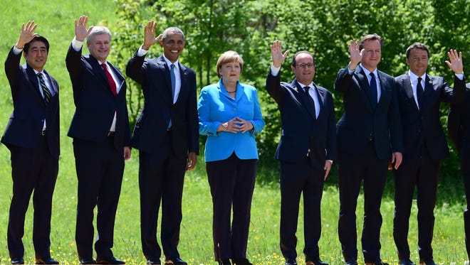 Japanese Prime Minister Shinzo Abe, Canada's Prime Minister Stephen Harper, President Obama, German Chancellor Angela Merkel, French President Francois Hollande, British Prime Minister David Cameron, and Italy's Prime Minister Matteo Renzi pose for a photo on their way to their first working session at the Elmau Castle near Garmisch-Partenkirchen, southern Germany, on June 7, 2015, at the start of a G-7 summit.