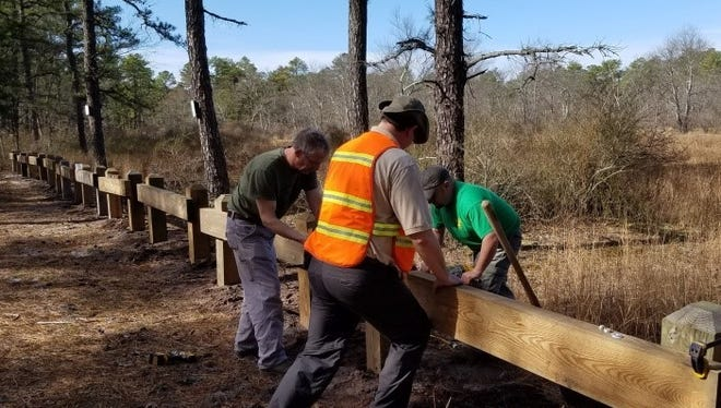 Volunteers from various groups that use the Pinelands install barriers around sensitive ponds as part of a state environmental project to help protect them from off-road and all-terrain vehicles that illegally damage them.