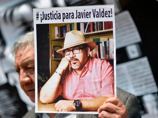 A journalist shows a picture of Mexican journalist Javier Valdez, murdered on the eve, during a protest by journalists in Mexico City on May 16, 2017.  Mexico ranks third in the world for the number of journalists killed, after Syria and Afghanistan, according to media rights group Reporters Without Borders.