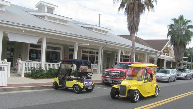 A golf cart sporting a Trump campaign placard is parked in front of a store in Sumter Landing, a community in The Villages, a solidly Republican stronghold an hour northwest of Orlando.