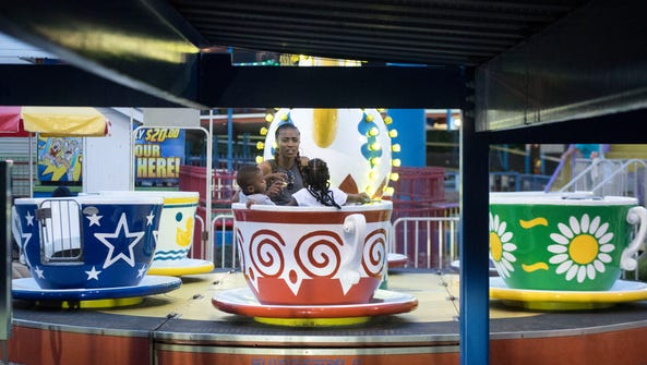 A family on the teacups ride at Fast Tracks amusement