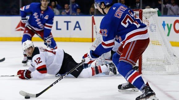 New York Rangers center Filip Chytil (72) looks to pass around New Jersey Devils defenseman Ben Lovejoy (12) in overtime of an NHL preseason hockey game Wednesday, Sept. 20, 2017, in New York. The Rangers won 4-3 in overtime. (AP Photo/Adam Hunger)