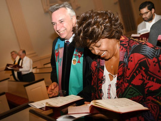 In this Tuesday, Nov. 8, 2016 photo, the Rev. Dr. James L. Brewer-Calvert, left, and Sylvia Gibbs sing during the Ecumenical Election Day Communion Service at the Decatur First United Methodist Church in Decatur, Ga. Democrats and Republicans shared the same pews, wearing voter stickers shaped like Georgia peaches, and shut out the barrage of news sweeping the country.