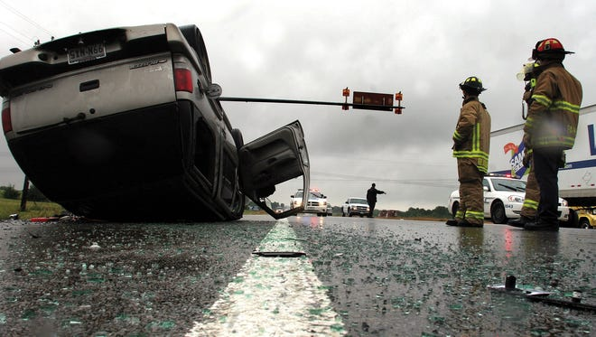 Paris, Texas, firefighters watch over the scene of a one-car rollover on May 29, 2007, as a Paris police officer directs traffic around the accident. Rain is the primary cause of most weather-related fatal car accidents in the USA.