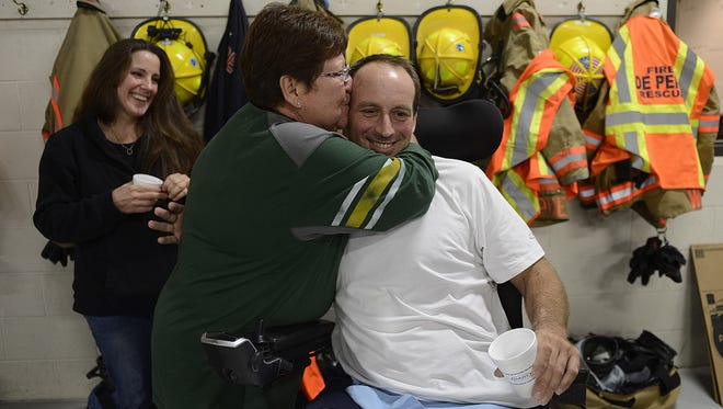 Sandra Marchant, of Green Bay, hugs and kisses Jason Pansier, a Ledgeview fire captain and department president who lost a leg after a farming accident, during a blood drive at the De Pere Fire Department on Friday. The event was in honor of Pansier and firefighters killed in the Sept. 11, 2001, terrorist attacks on the World Trade Center.