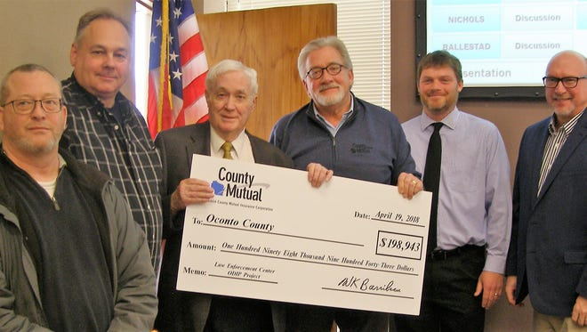 Former Oconto County Board chairman Lee Rymer, second from left, holds ceremonial check of the rebate in workman's compensation rebate from the Law Enforcement Center project. From left are Curt Schleicher, project manager of Samuels Group; Tim Harmann, project superintendent of Samuels Group; Rymer; John Dirkse, executive vice president Wisconsin County Mutual Insurance Co.; Kurt Berner, vice president of Samuels Group; and Vance Forrest, vice president of risk management, Wisconsin County Mutual Insurance. Rymer served as president of the County Mutual Board for many years. Samuels Group, Wausau, was the county's construction manager for the new jail and sheriff's office, which opened last summer.