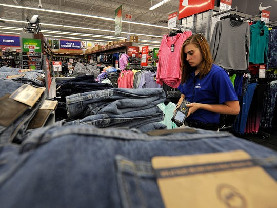 Katie Radcliff checks a display before opening on Black Friday at Academy Sports + Outdoors in Jackson, Tenn., on Nov. 25, 2016.