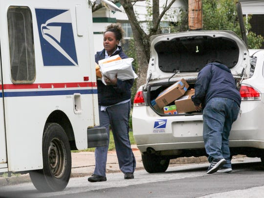 Karmesha Lindsay, left, and Pam Chapman work with the U.S. Post Office in Anderson on Monday, transferring packages from a vehicle to a postal carrier truck for delivery.