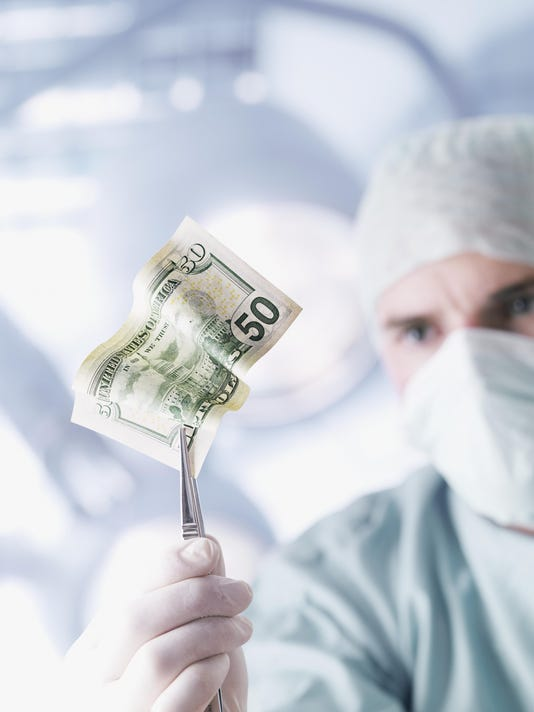 Doctor holding a fifty dollar bill with tweezers