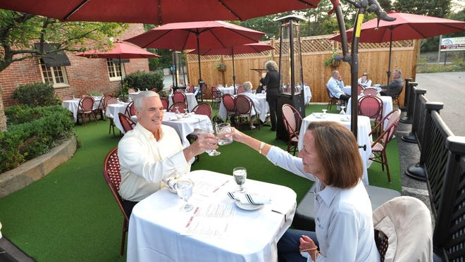 Gary and Patty Bacon of Quincy toast a warm summer evening on the Cafe DeParis outdoor dining patio at the Common Market restaurant on Willard Street in Quincy, Tuesday, Sept. 15, 2020. Tom Gorman/For The Patriot Ledger