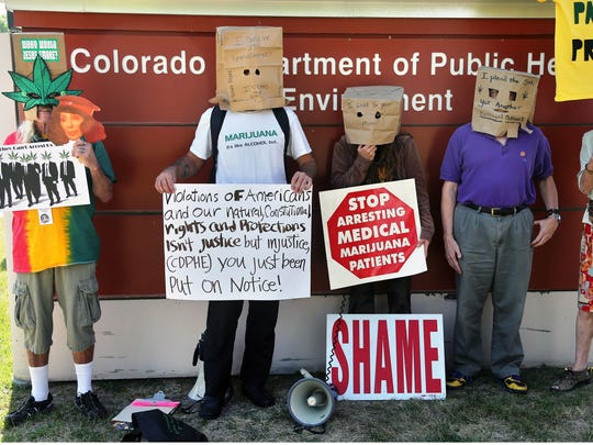 Medical marijuana patients wear paper bags over their heads during a protest against alleged state government security breaches in Denver on Aug. 21.