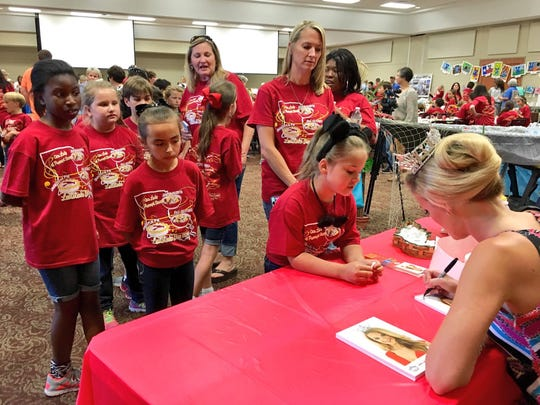 Miss Louisiana April Nelson signs autographs Tuesday for a line of third-graders at Our Lady of Prompt Succor School during its annual Louisiana Day celebration.