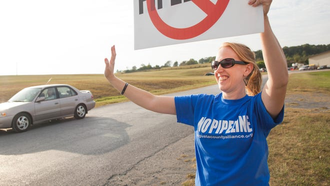 Protesting the construction of Dominion's Atlantic Coast Pipeline, Jennifer Lewis, of Waynesboro, waves to passing  cars outside of the open informational meeting hosted by the energy company at Augusta Expo on Monday, Sept. 15, 2014.