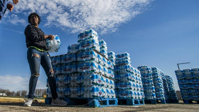 Katia Kenney, 18 of Flint, Mich., volunteers as she loads cases of water into vehicles as non-profit Pack Your Back distributes more than 37,000 bottles of water on Monday, April 22, 2019, at Dort Federal Event Center in Flint.