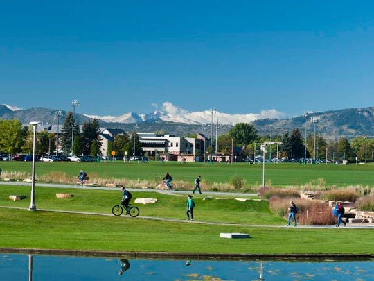 Students walk on the West Lawn of the Colorado State University in the with snow on Longs Peak in the background and the Lagoon in the foreground.