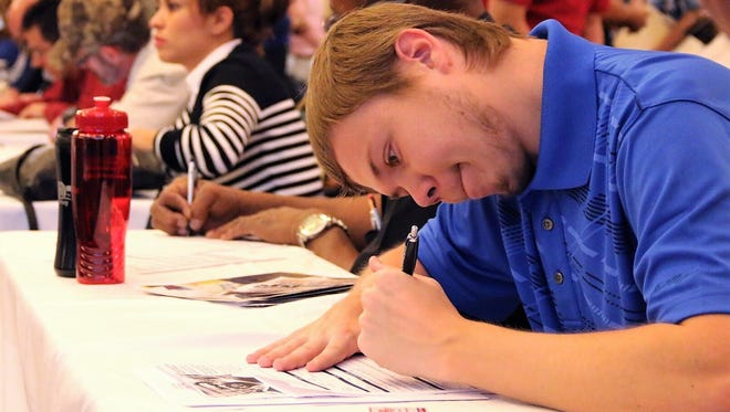A young man fills out paperwork at a Workforce Solutions Borderplex job fair for people with disabilities. The public employment agency has launched its annual summer jobs programs for youths with disabilities and youths from low-income families.