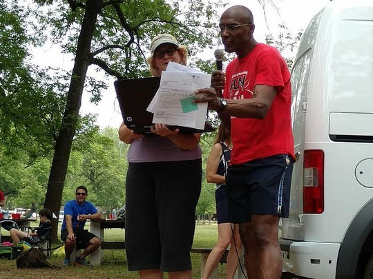 """Ray Petit and longtime volunteer/assistant and bus director Janice Reid present awards following last year's Towpath """"Train""""ing Run at the picnic in Johnson Park."""