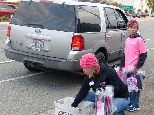 Erika Wiechman, president of the Nor-Cal Think Pink board of directors, and her 10-year-old son, Colton, distribute free Think Pink Day bags.