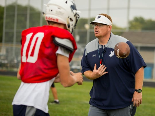 Roosevelt High School head coach Erik Link tosses the ball to Sam Knoshaug, senior, as he talks to the team during practice Monday, Sept. 18, 2017, in Des Moines, Iowa. Roosevelt enters district play at 3-1 overall. They won just three games all of last season.