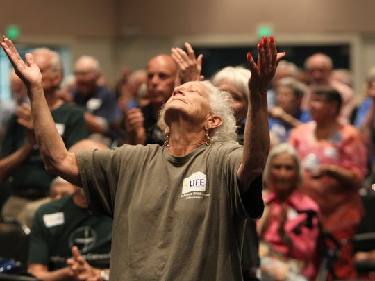 Worshipper Rae smith lifts her hands in praise during an action assembly held by the Lee Interfaith for Empowerment, or LIFE, at  Harborside Event Center Monday.