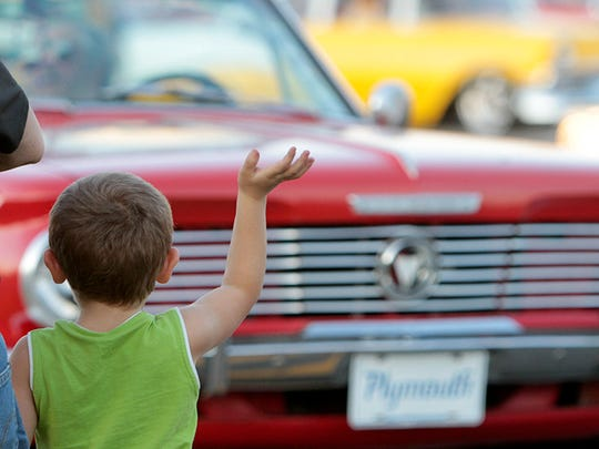In this photo taken on Monday, Oct. 8, 2012, Andrew Cooper, 4, of Gulfport, Miss., waves to the classic cars during the Cruisin' The Coast parade in Long Beach, Miss.,