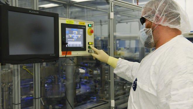 Arik Smith operates a stacking machine at EaglePicher Industries in Joplin, Mo.