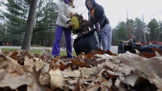 Junior high students bag leaves they raked in a yard in Wisconsin Rapids during the 2012 United Way of Inner Wisconsin Day of Caring.
