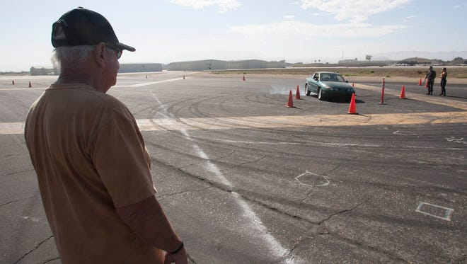 """In this 2013 photo, stunt man and coordinator Jim Wilkey, left, watches a student in his stunt driving class attempt to complete a """"box 90"""" maneuver, in which the driver puts the car into a skid and slides sideways into a spot. Wilkey teaches the class at the Camarillo Airport for Bobby Ore Motorsports."""
