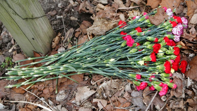 A bouquet of flowers placed below a sign marking the Monon High Bridge Trail Tuesday, February 21, 2017, just east of Delphi. Delphi teens Liberty German, 14, and Abigail Williams, 13, were hiking the Delphi Historic Trails the afternoon of February 13, but did not show up when relatives arrived later to pick them up. The girls were reported missing at 5:30 p.m. Their bodies were discovered by searchers about 12:15 p.m. Tuesday east of High Bridge and about 50 feet north of Deer Creek.