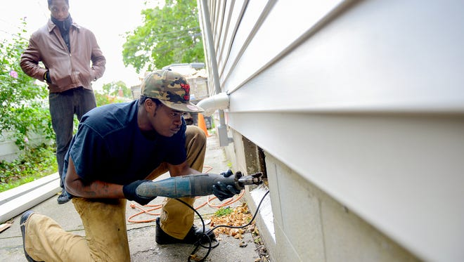 """Dominique Anderson works on cutting out the frame of an old basement window that will be replaced with a glass block window Sept. 14, 2016 in Lansing. Anderson is working with Michael McKissic rehabbing in Lansing through McKissic's Mikey 23 Foundation. The foundation is named after his son, Mike McKissic II, who was shot and killed in 2015. The house was destroyed by fire and the foundation, which teaches young men construction trade skills, is rebuilding it and hopes to use the proceeds to further their mission. Anderson has been working for McKissic for about six months and said of his boss: """"It's amazing. He teaches us the right way. He's an awesome man. He motivates us everyday to get up and work. It's positing. I like doing positive things."""""""