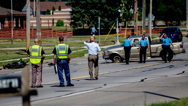 Lansing police investigate the scene of a fatal motorcycle-truck crash on South Martin Luther King Jr. Blvd. at Northrup St. on Wednesday, Sept. 20, 2017, in Lansing. The driver of a motorcycle was taken to the hospital with life-threatening injuries and later died. The two occupants of the truck were treated at the scene.