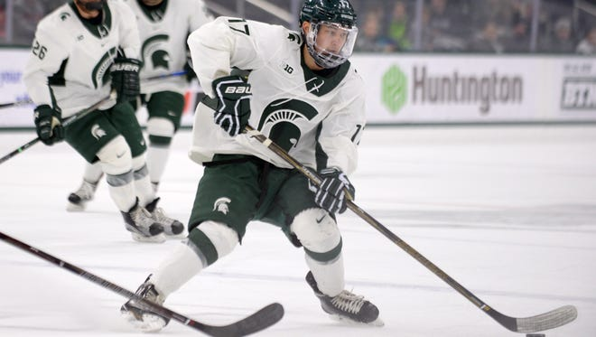 Freshman forward Taro Hirose moves the puck down the ice during the game against Northeastern on Sunday, Dec. 18, 2016 at Munn Ice Arena.