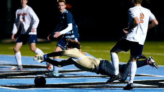 Lansing Catholic goal keeper Matthew Benivegna dives on a ball kicked by Flint Powers' Kyle Genord, right, during the second half on Thursday, Oct. 26, 2017, in Lansing