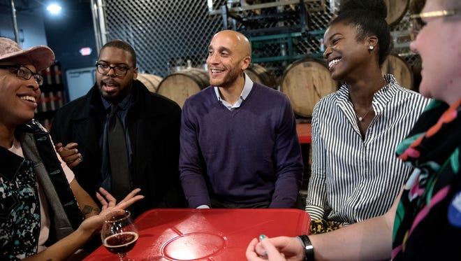 Lansing City Council 4th Ward candidate Brian Jackson, center, and his wife Arielle, right, celebrate Jackson's win with friends, from left, Jhevon Shaw, Derrell Slaughter and Jessica Fowler, far right, on Tuesday, November 7, 2017, at the Lansing Brewing Company.