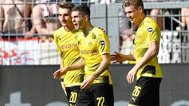 Dortmund's Christian Pulisic, center, reacts surprised after scoring during the German Bundesliga soccer match between Borussia Dortmund and VfB Stuttgart in Dortmund, Germany, Sunday, April 8, 2018.
