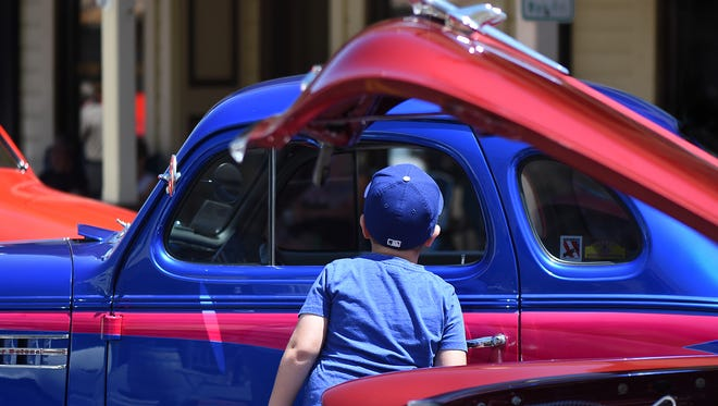 A boy stops on to take a look inside a classic car at the Classic Car Show-N-Shine in Virginia City on Friday, Aug. 3, 2018. Hot August Nights began in Virginia City on Friday and continues in Reno and Sparks through Aug. 12.