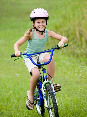 girl riding bicycle on the grass