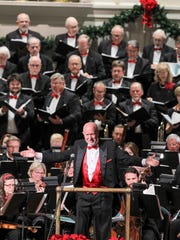 Conductor Don Campbell, of Southern Wesleyan University, acknowledges the audience's applause at GAMAC's Christmas Cheer concert Saturday at Boulevard Baptist Church.